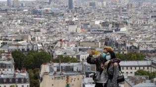 Un couple se prend enphoto devant le Sacré-Coeur, à Paris, le 27 août 2020. (LUDOVIC MARIN / AFP)