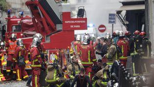 Les pompiers, exténués, après leur interventionpour éteindre l'incendie, rue de Trévise, à Paris. (GEOFFROY VAN DER HASSELT / AFP)