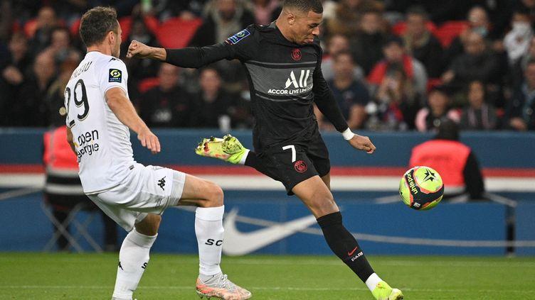 Kylian Mbappé face à Vincent Manceau lors de la 10e journée de Ligue 1 opposant le PSG à Angers, le 15 octobre 2021 au Parc des Princes. (ANNE-CHRISTINE POUJOULAT / AFP)