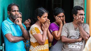 DesSri Lankaisregardent les forces de sécurité inspecter un véhicule suspectau lendemain des attentats, le 22 avril 2019, à Colombo (Sri Lanka). (CHAMILA KARUNARATHNE / ANADOLU AGENCY / AFP)