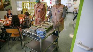 Des employées de la ville servent les repas aux enfants dans une ecole primaire de Valence, le 1er septembre 2020. (NICOLAS GUYONNET / HANS LUCAS)