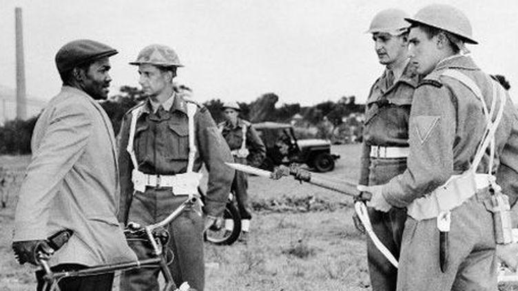 Des militaires sud-africains blancs contrôlent un Noir à Nyanga, près du Cap, le 2 avril 1960. (AFP)