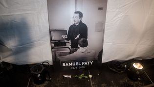 Un portrait de Samuel Paty posé à terre lors d'une marche blanche en hommage au professeur d'histoire-géographie, le 20 octobre 2020 à Conflans-Sainte-Honorine (Yvelines). (MICHAEL BUNEL / LE PICTORIUM / MAXPPP)