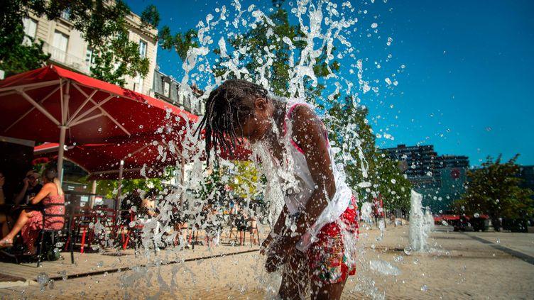 Un enfant se rafraîchit pendant un épisode de fortes chaleurs, en juin 2020.  (MAXPPP)