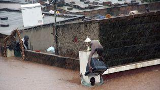 AMaputo, des habitants récupèrent ce qui leur reste après les fortes inondations qui touchent le sud du Mozambique - 15 janvier 2013 (STRINGER / AFP)
