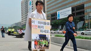 Seul, un militant sud-coréen manifeste à Séoul, le 3 juin, 2013. Il montre le portrait de neuf fugitifs nord-coréens, dont cinq mineurs. On peut lire au-dessus de la photo: «N'oubliez pas les enfants.» (AFP PHOTO / JUNG YEON-JE)