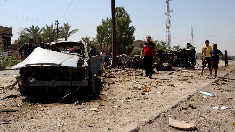 Des passants inspectent la carcasse d'une voiture piégée, jeudi 15 août 2013, à Bagdad (Irak). (ALI AL-SAADI / AFP)