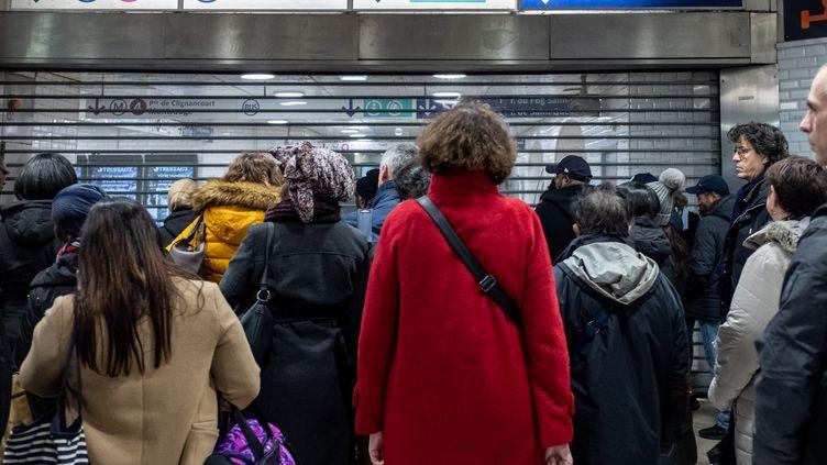 Des usagers du réseau RATP attendent devant l'entrée du métro 4, en pleine grève contre la réforme des retraites, à Paris le 9 décembre 2019. (SAMUEL BOIVIN / NURPHOTO / AFP)