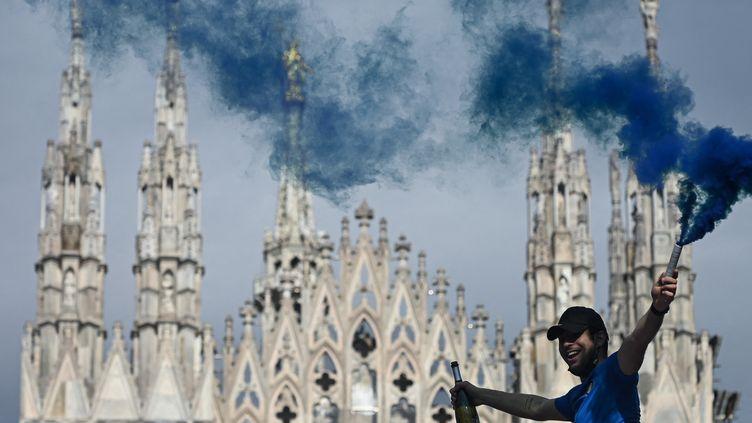 Un supporter de l'Inter célèbre le titre de champion d'Italie sur la Piazza Duomo. (PIERO CRUCIATTI / AFP)