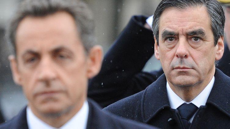 L'ancien président de la République, Nicolas Sarkozy, et son ancien Premier ministre, François Fillon, le 11 novembre 2010 à Paris. (MIGUEL MEDINA / AFP)