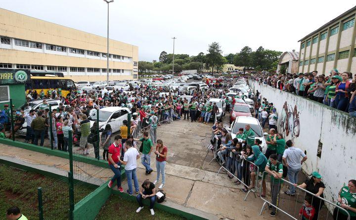 Des supporters de Chapecoense réunis devant l'Arena Conda, le 29 novembre 2016, à Chapeco (Brésil). (PAULO WHITAKER / REUTERS)