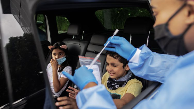 Des enfants testés Covid-19 dans une voiture à Johannesbourg (Afrique du Sud) (LUCA SOLA / AFP)