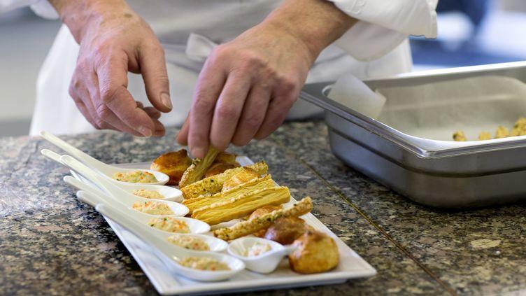 Le chef français Alain Lecossecprépare un plat dans la cuisine du restaurant d'enseignement de l'institut Paul Bocuse à Ecully, près de Lyon (Rhône-alpes), le 11 Décembre 2013. (© ROBERT PRATTA / REUTERS / X00222)
