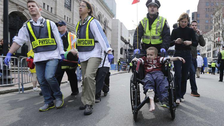 Les secours évacuent un petit blessé après les explosions. (CHARLES KRUPA / AP / SIPA)