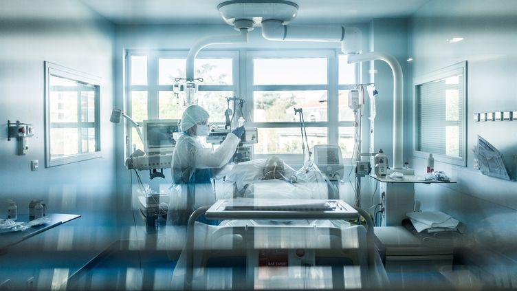 Unsoignant au chevet d'un malade du Covid-19 dans une clinique de Lyon, le 3 avril 2020. (NICOLA VIGILANTI / HANS LUCAS / AFP)