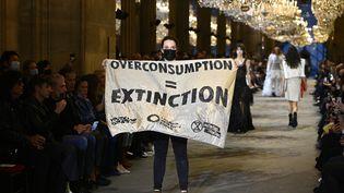 Incursion de militants pour le climat au défilé Louis Vuitton printemps-été 2022 à laParis Fashion Week, le 5 octobre 2021 (CHRISTOPHE ARCHAMBAULT / AFP)