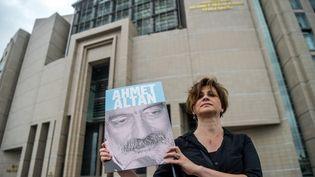 Une journaliste turque pose avec une photo d'Ahmet Altan devant le Palais de Justice d'Istanbul, le 18 juin 2017. (OZAN KOSE / AFP)
