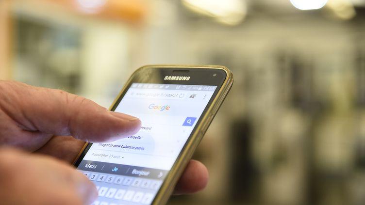 Un homme utilise son téléphone portable dans le métro à Paris, le 25 août 2016. (BERTRAND GUAY / AFP)