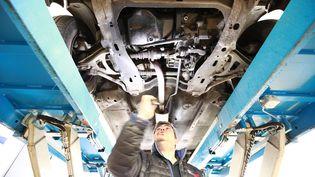 Un employé d'un centre de contrôle technique inspecte une voiture, le 4 mai 2018 à Drancy (Seine-Saint-Denis). (MAXPPP)