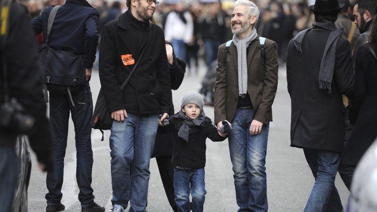 """Un couple d'hommes et un enfant participent à la manifestation en faveur du projet de loi sur le """"mariage pour tous"""", le 16 décembre 2012, à Paris. (FRED DUFOUR / AFP)"""