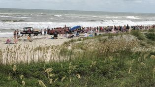 Des vacanciers forment une chaîne humaine pour sauver des baigneurs sur la plage de Emerald Isle en Caroline du Nord (Etats-Unis), le 25 juillet 2018. (SHANE GENTRY)