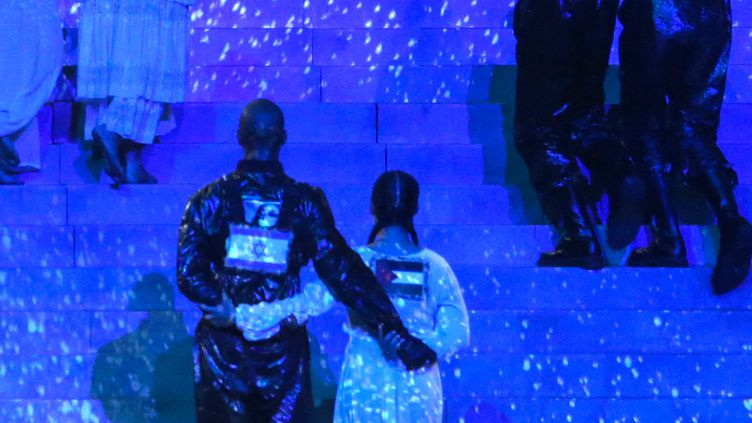 Deux danseurs de Madonna arborent des drapeaux israélien et palestinien sur la scène de l'Eurovision, le 18 mai 2019, à Tel Aviv. (ORIT PNINI / KAN / AFP)