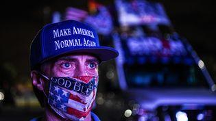 """Un supporteur du partie démocrate porte une casquette """"Make America Normal Again"""", lors de la soirée électorale du mardi 3 novembre 2020, à Miami, en Floride. (CHANDAN KHANNA / AFP)"""
