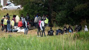 Un groupe de migrants est réuni, le 21 juin 2017, près de la route qui mène au port de Calais. (DENIS CHARLET / AFP)