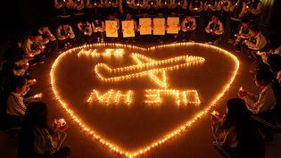 Des familles des passagers chinois du vol MH370 de la Malaysia Airlines, disparu début mars 2014, prient, le 10 mars 2014 àZhuji (Chine). ( AFP )