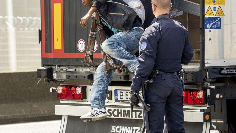 Un CRS fait descendre un migrant d'un camion, le 3 juin 2015 à Calais (Pas-de-Calais). (PHILIPPE HUGUEN / AFP)