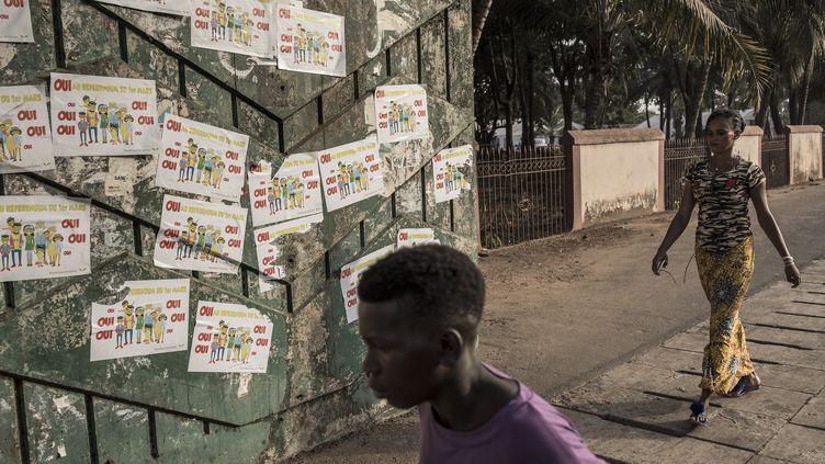 """Des habitants de Conakry (Guinée) se baladent devant un mur où des affiches """"Oui au référendum"""" ont été collées, le 26 février 2020. (JOHN WESSELS / AFP)"""
