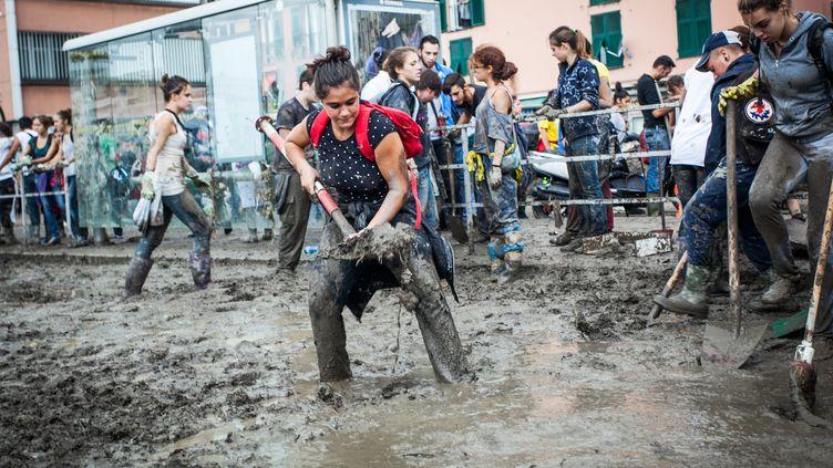 Des volontaires nettoient les rues de Gênes (Italie) envahies par la boue après de violents orages, le 11 octobre 2014. (SABRINA DE POLO / NURPHOTO / AFP)