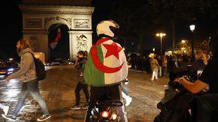 Des supporters de l'Algérie fêtent la victoire de l'Algérie en demi-finale de la Coupe d'Afrique des nations, le 14 juillet 2019, à Paris. (ZAKARIA ABDELKAFI / AFP)