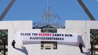Des manifestants déploient une banderole, le 1er décembre 2016, au Parlement à Canberra (Australie) pour réclamer la fermeture des camps de détention offshore de migrants. (NATHANIAL HOWELLS / AFP)