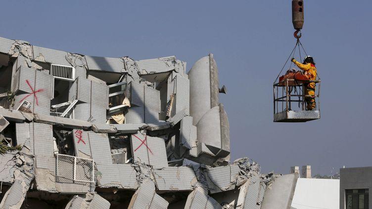 Des secouristes extraient un corps du bâtiment de 17 étages qui s'est effondré, à Tainan, après le séisme du 6 février 2016. (TYRONE SIU / REUTERS)