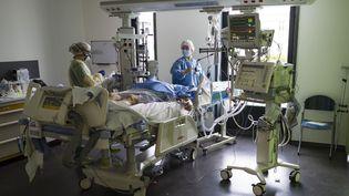 Des soignants prennent en charge un patient atteint du covid-19 à l'hôpital Louis-Pasteur de Colmar (Haut-Rhin), le 26 mars 2020. (SEBASTIEN BOZON / AFP)