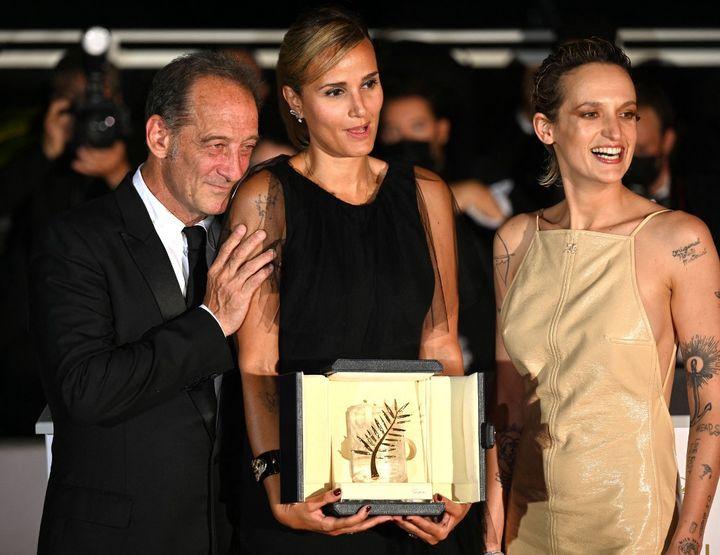 """La réalidatrice française Julia Ducournau pause avec sa Palme d'or pour """"Titane"""", entourée de son acteur Vincent Lindon et de son actrice Agathe Rousselle, au 74e festival de Cannes (2021). (MUSTAFA YALCIN / ANADOLU AGENCY)"""