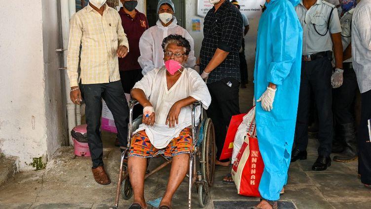 Le personnel de l'hôpital Vijay Vallabh à Bombay (Inde)transfère une patiente après qu'un incendie s'est déclaré dans l'établissement, le 23 avril 2021. (PUNIT PARANJPE / AFP)