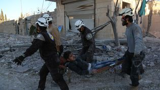 """Des secouristes des """"Casques blancs"""" syriens évacuent un blessé après un bombardement à Alep, le 18 novembre 2016. (BEHA EL HALEBI / ANADOLU AGENCY / AFP)"""