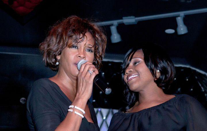 Whitney Houston au côté de la chanteuse Kelly Price, le 9 février 2012 à Hollywood. (GABRIEL OLSEN / FILM MAGIC / GETTY IMAGES)