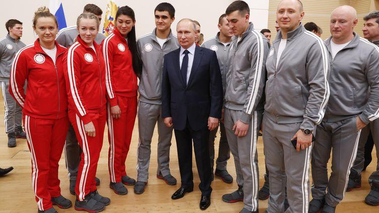 Le président russe Vladimir Poutine pose avec des athlètes russes qui participent aux JO d'hiverde 2018 à Pyeongchang. (GRIGORY DUKOR / POOL / REUTERS POOL)