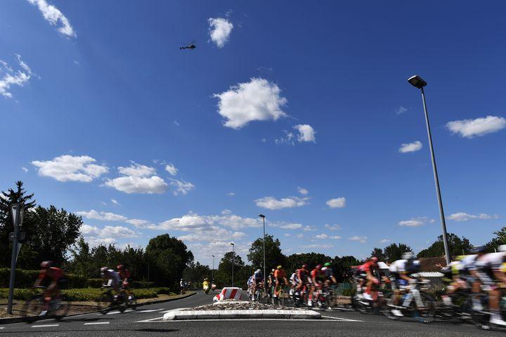 Le peloton se scinde en deux pour franchir un rond-point lors de l'étape entre Saint-Flour (Cantal) et Albi (Tarn), le 15 juillet 2019. (JEFF PACHOUD / AFP)