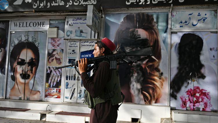 Un taliban devant un salon de beauté dont les visages de femmes en vitrine ont été occultés, à Kaboul (Afghanistan), le 18 août 2021. (WAKIL KOHSAR / AFP)