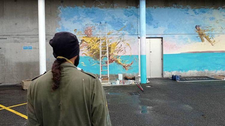 L'artiste Bust the drip devant sa dernière oeuvre réaliséesur le mur Est du Sporting d'Este de la ville de Billère (Pyrénées-Atlantique) (Mairie de Billère)