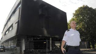 Un policier se tient devant le centre des impôts àMorlaix, le 20 septembre 2014, au lendemain de l'incendie. (FRED TANNEAU / AFP)