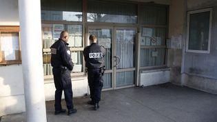 Des policiers surveillentl'entrée de l'école maternelleJean-Perrin à Aubervilliers, le 14 décembre 2015. (CHARLES PLATIAU / REUTERS)