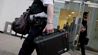 Un policier quitte le siège d'Alstom à Londres (Royaume-Uni), le 24 mars 2010, après l'arrestation de trois responsables soupçonnés de corruption. (WARREN ALLOTT / AFP)