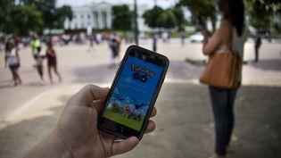 """Un homme joue à """"Pokémon Go"""" à Washington, aux Etats-Unis, le 12 juillet 2016. (JIM WATSON / AFP)"""