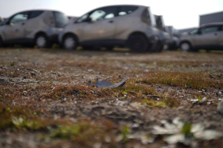 Des débris de plastique, de pneuset de plaques minéralogiques parsèment le terrain vague où sont stationnées les Autolib'. (PIERRE-LOUIS CARON / FRANCEINFO)