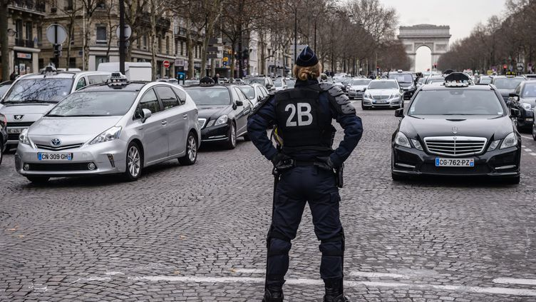 Un officier de police surveille une manifestation de taxis,qui bloque un accès à la porte Maillot, à Paris, le 28 janvier 2016. (MAXPPP)